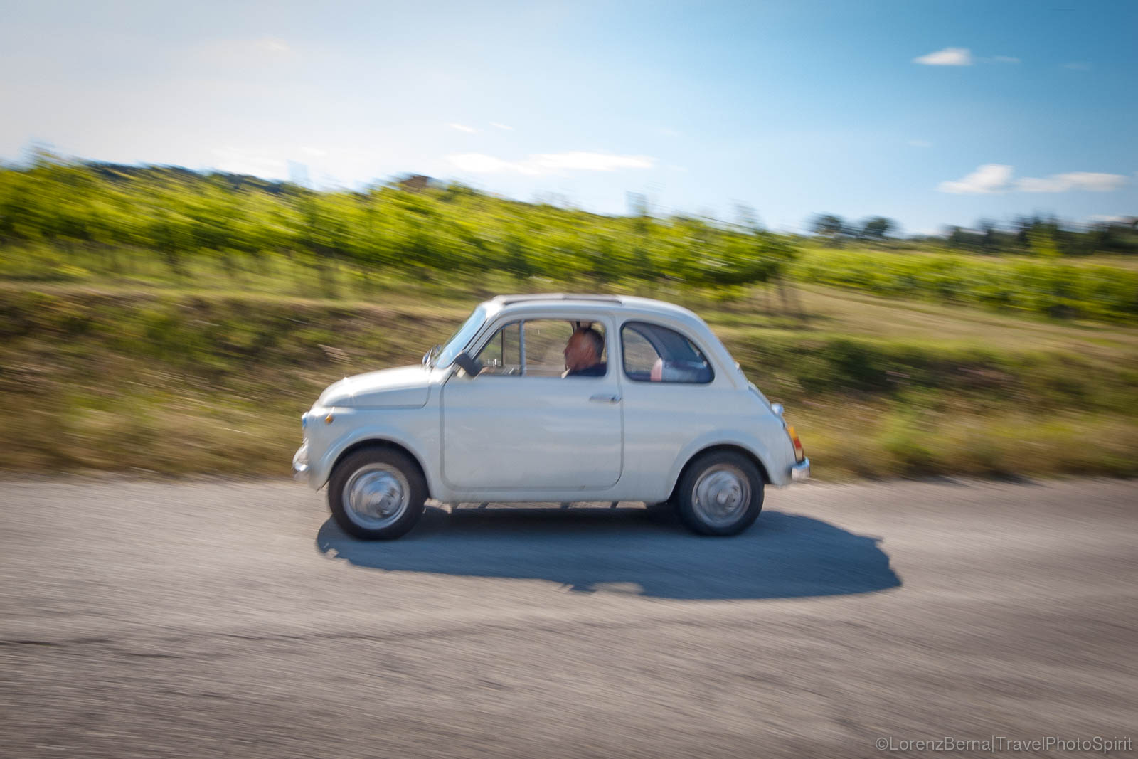 An old Fiat 500 driving on the roads of Tuscany, Italy