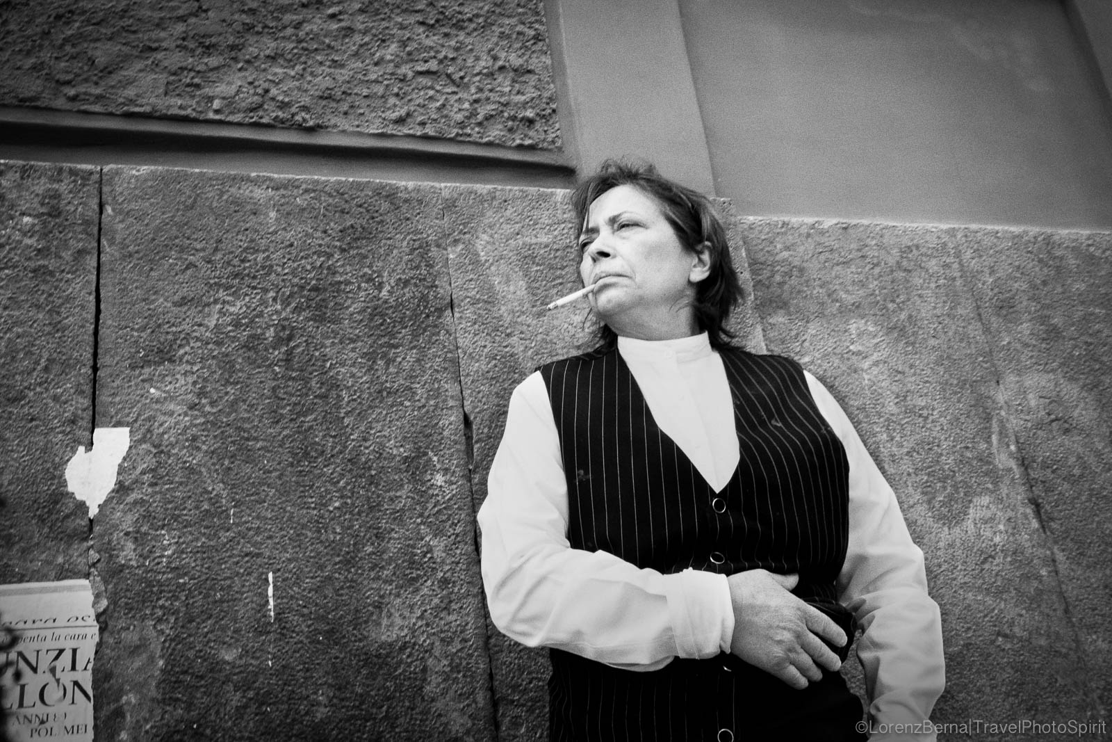 Naples style : a woman is smoking a cigarette alongside a wall, in a masculine outfit and expression - Naples, Italy