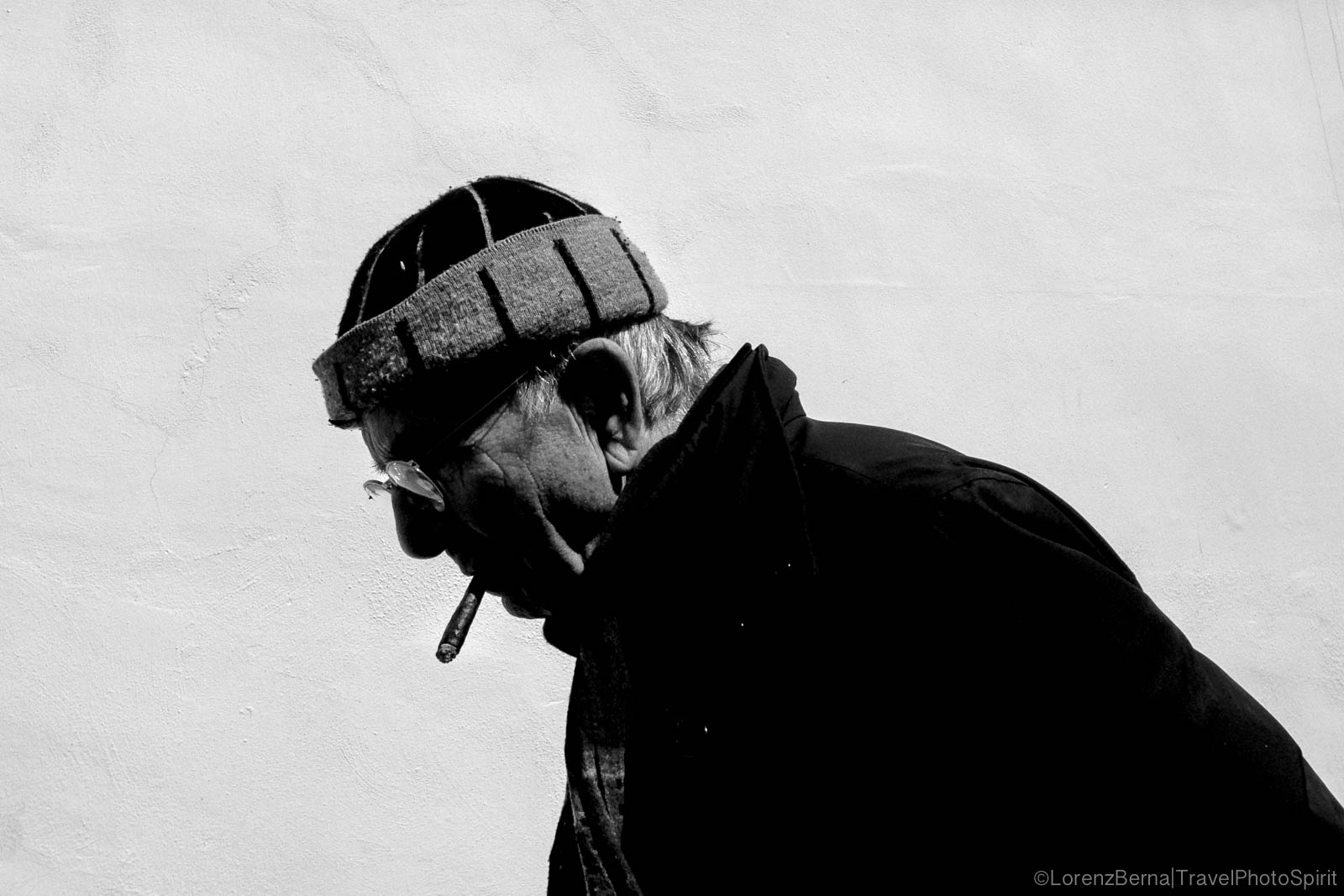 Street Photography in Naples : an old man walking with a cigarette on lips.