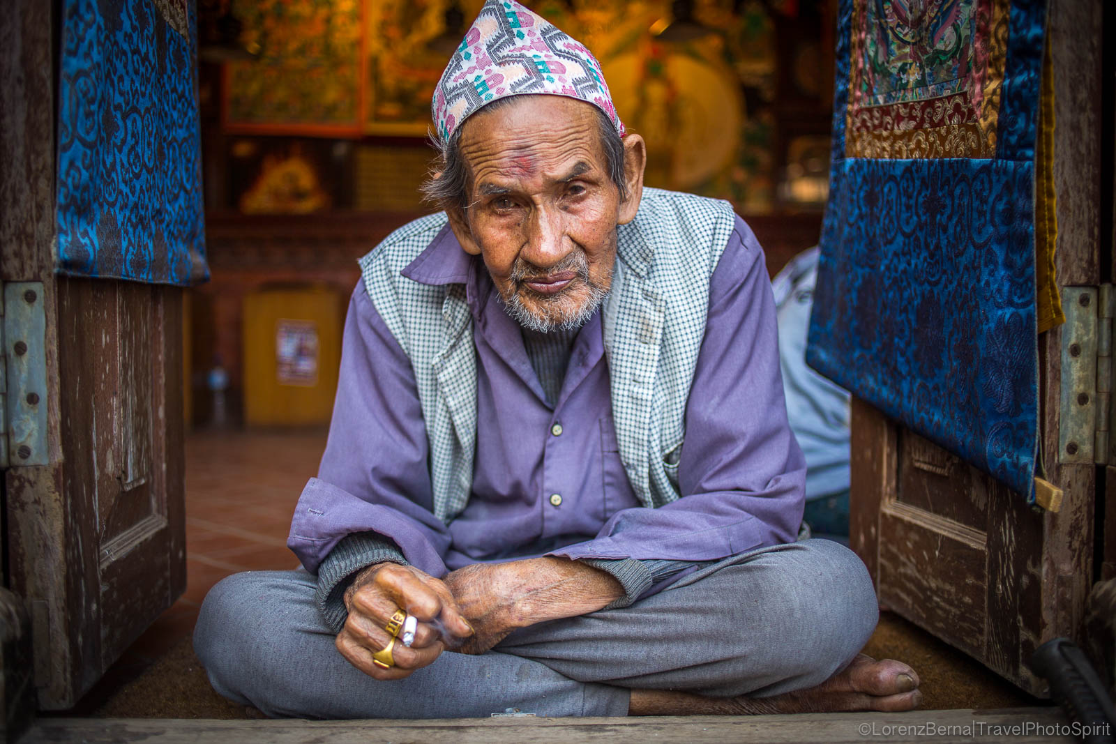 Old thangka painter smoking at the entry of his shop, in Bhaktapur - Travel Photography of Nepal by Lorenz Berna