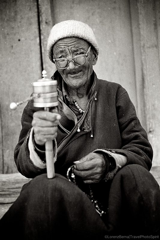 Portrait of an old Tibetan man praying in Leh. A Lorenz Berna Travel Photography of India