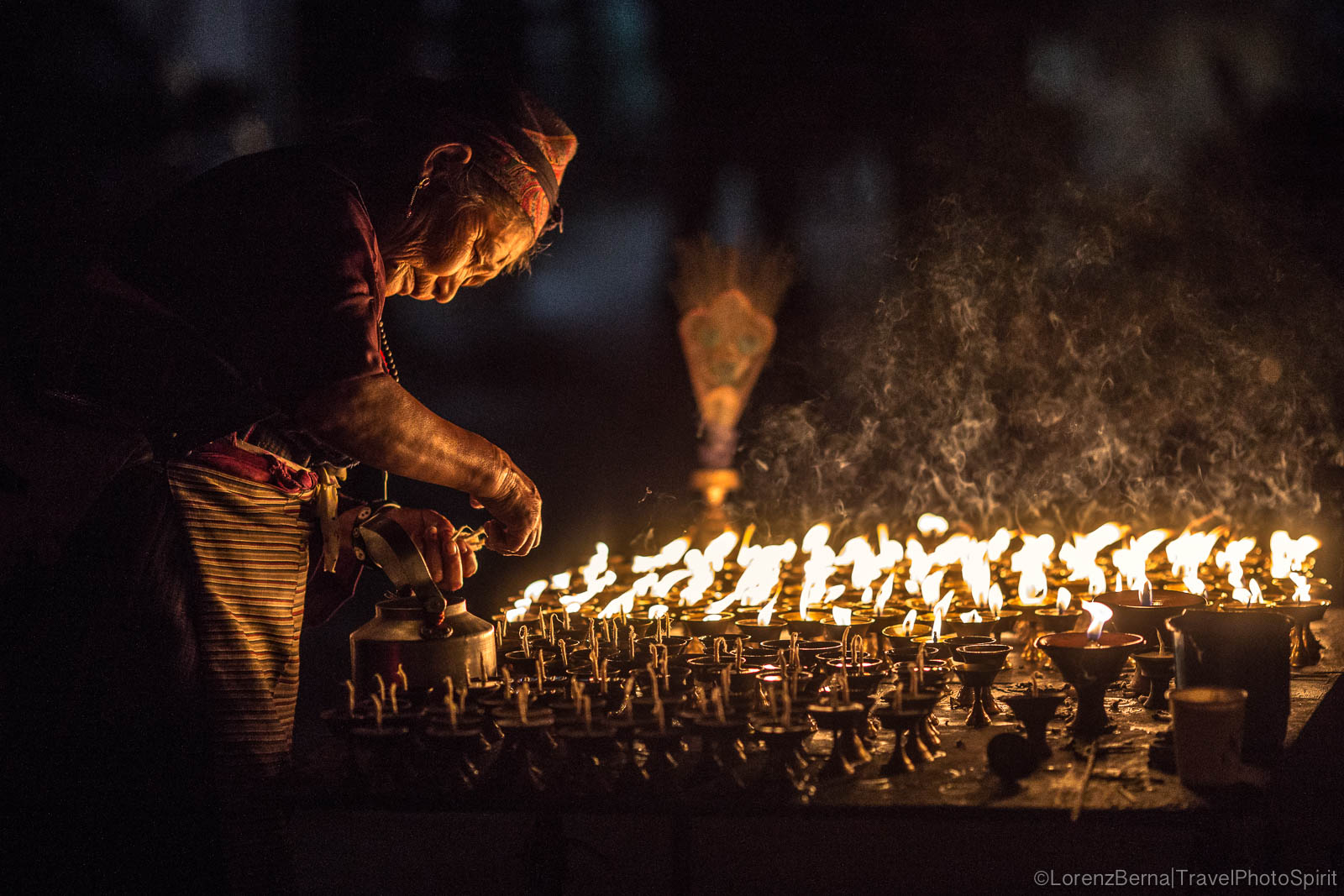 Tibetan woman lighting butter candles in Boudhanath quarter, Kathmandu - Nepal Travel Photography by Lorenz Berna