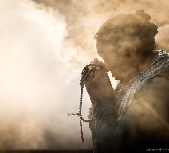 Woman praying, enveloped in the smoke of incese, with a mala in her hands - Travel Photography of Nepal by Lorenz Berna