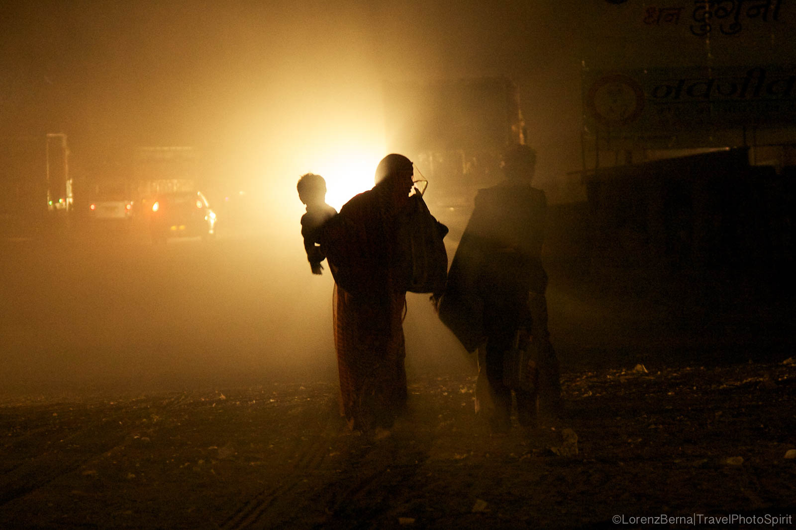 A Mother is walking in the streets of Pushkar by night, holding her child in her arms - A Lorenz Berna Photography of India