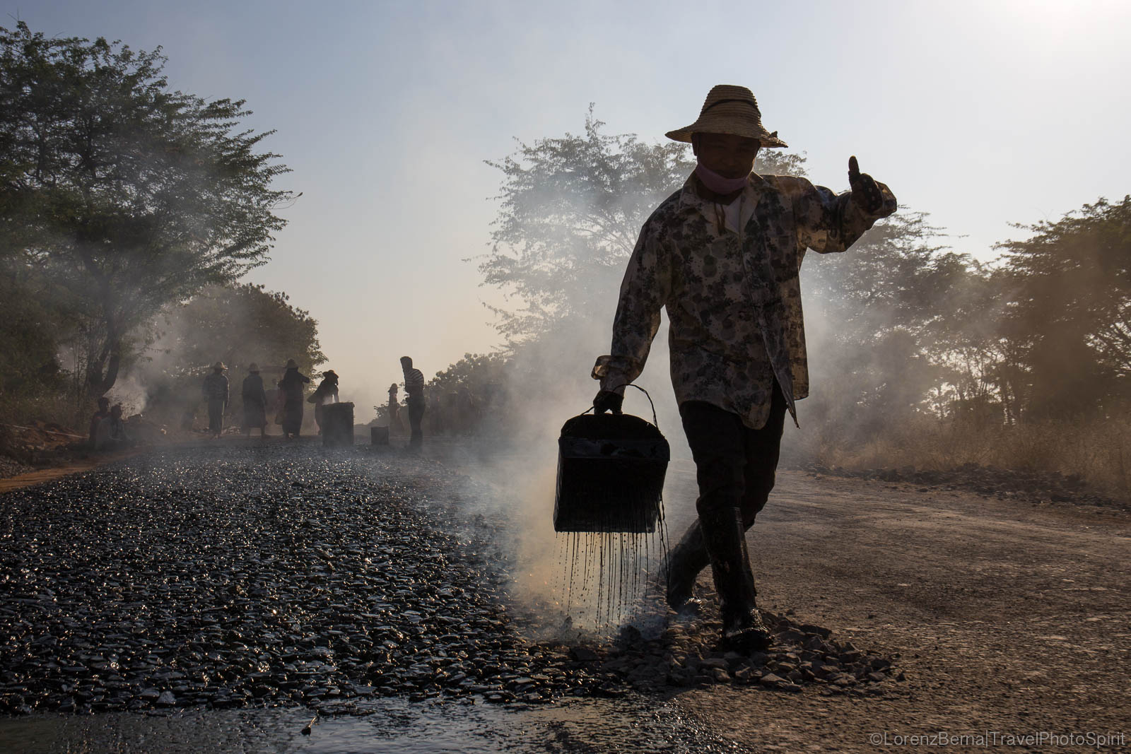 Workers pouring tar on a road in Myanmar