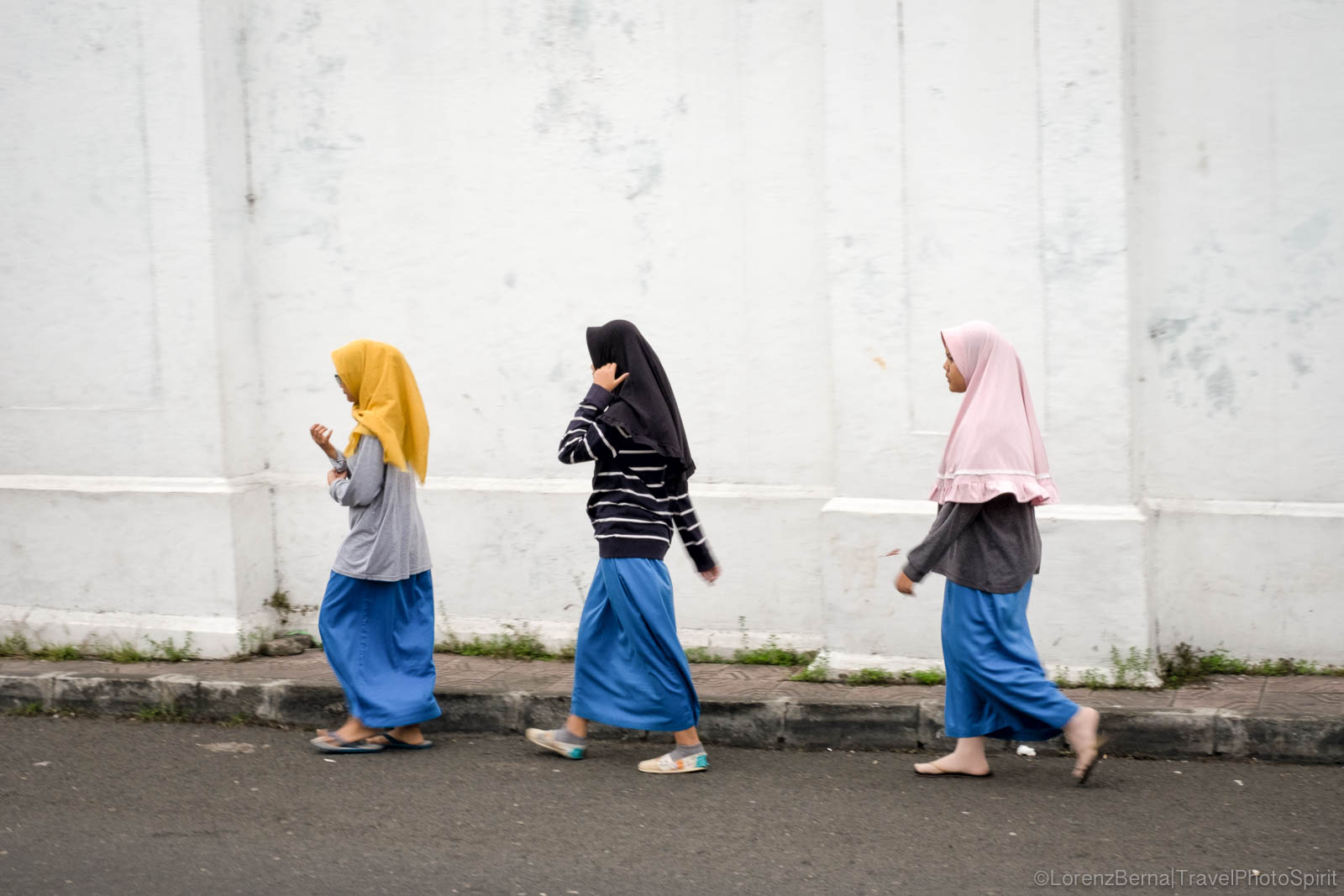 Three young Muslim girls walk on Yogyakarta street, Java, Indonesia.
