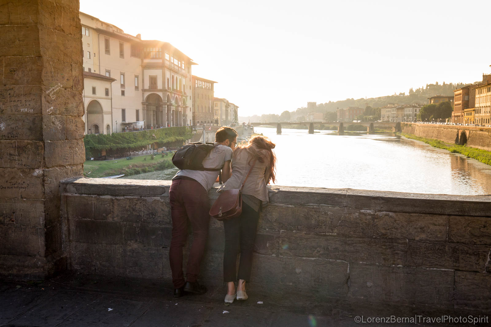 A couple is looking at the Arno river on the Ponte Vecchio, at sunrise, Florence, Tuscany, Italy.