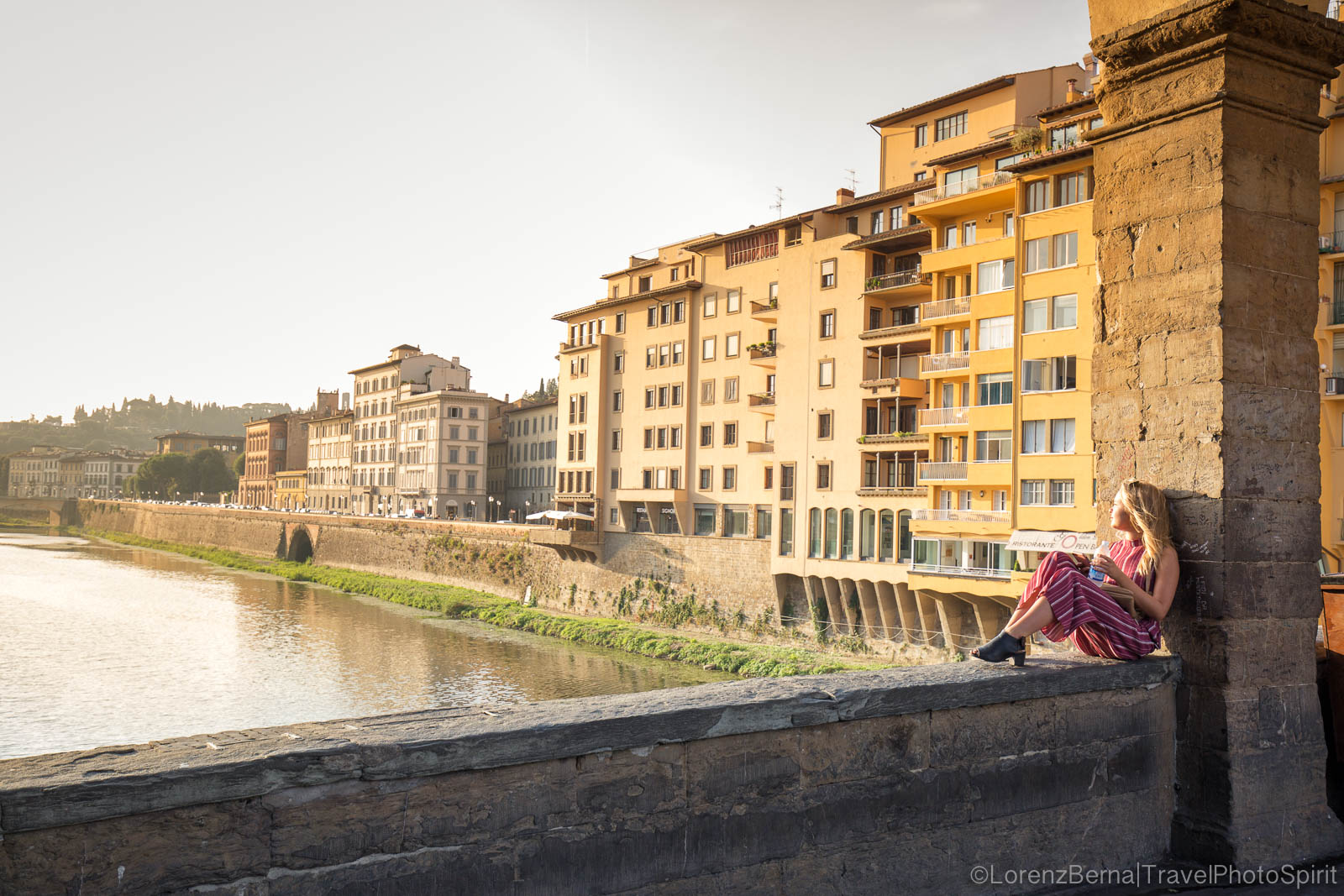 Tourist enjoying the first light of the morning from the Ponte Vecchio, Florence, Tuscany, Italy.