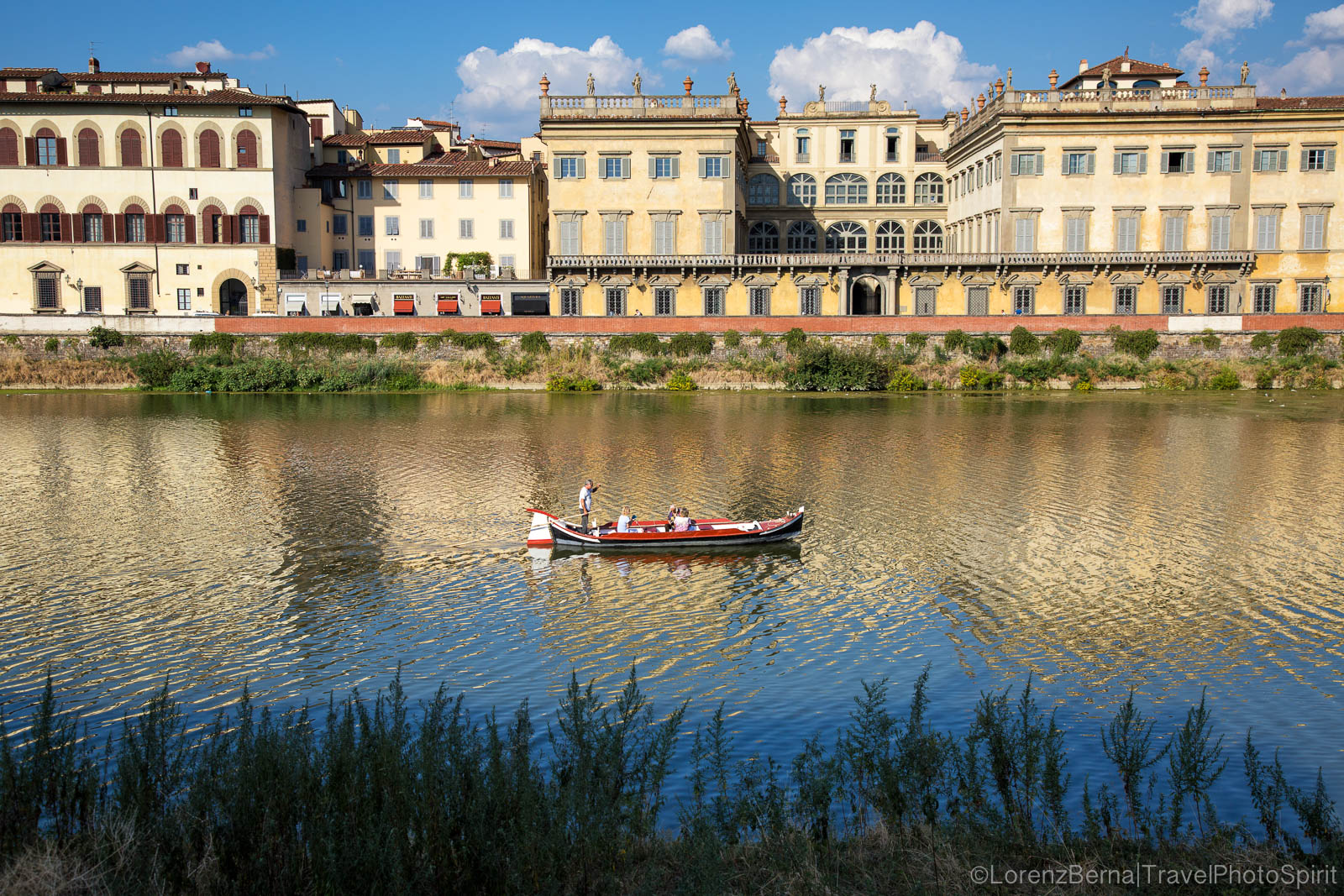 Small boat crossing the Arno River in Florence, Tuscany, Italy.