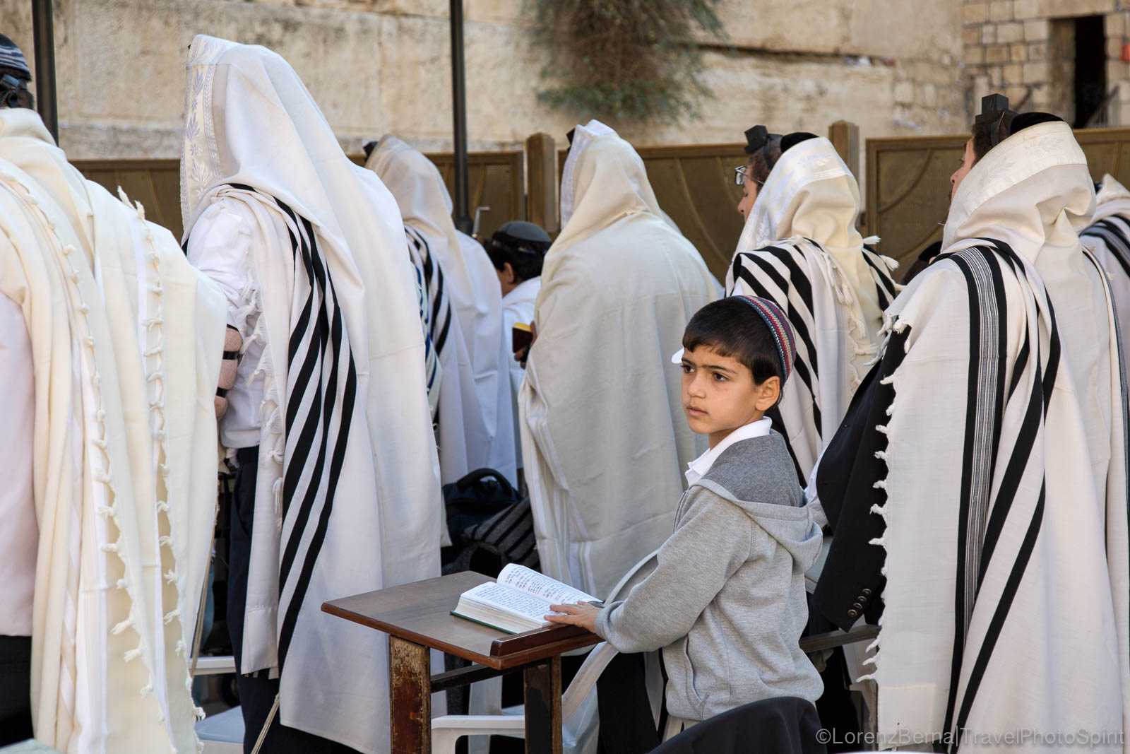 Young boy reciting the Torah among Jewish men, in the Jerusalem Old City.