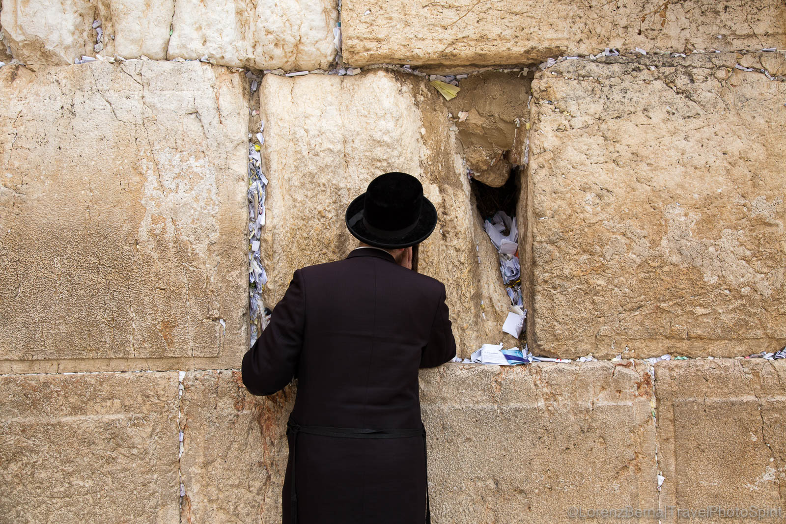 Man praying at the Wailing Wall, after having placed a paper containing his prayers to God, within the wall, Jerusalem, Israel.