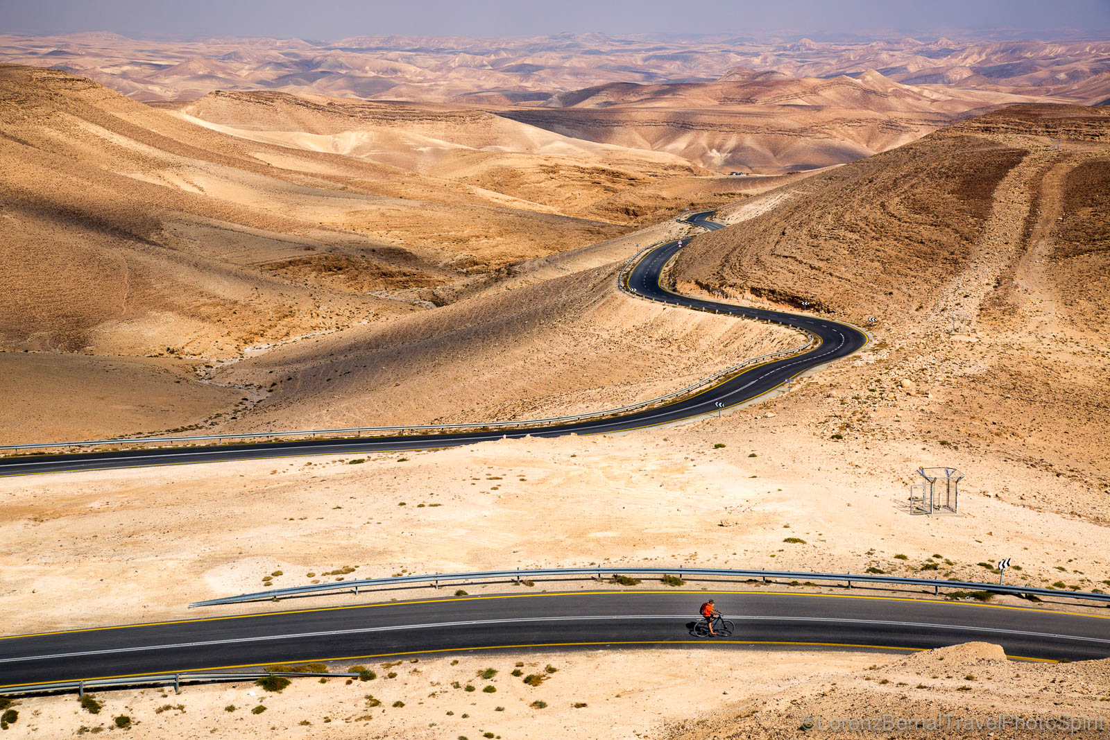 A bicycle rider on the winding roads going through the rocky valleys of the Judean Desert, Israel.