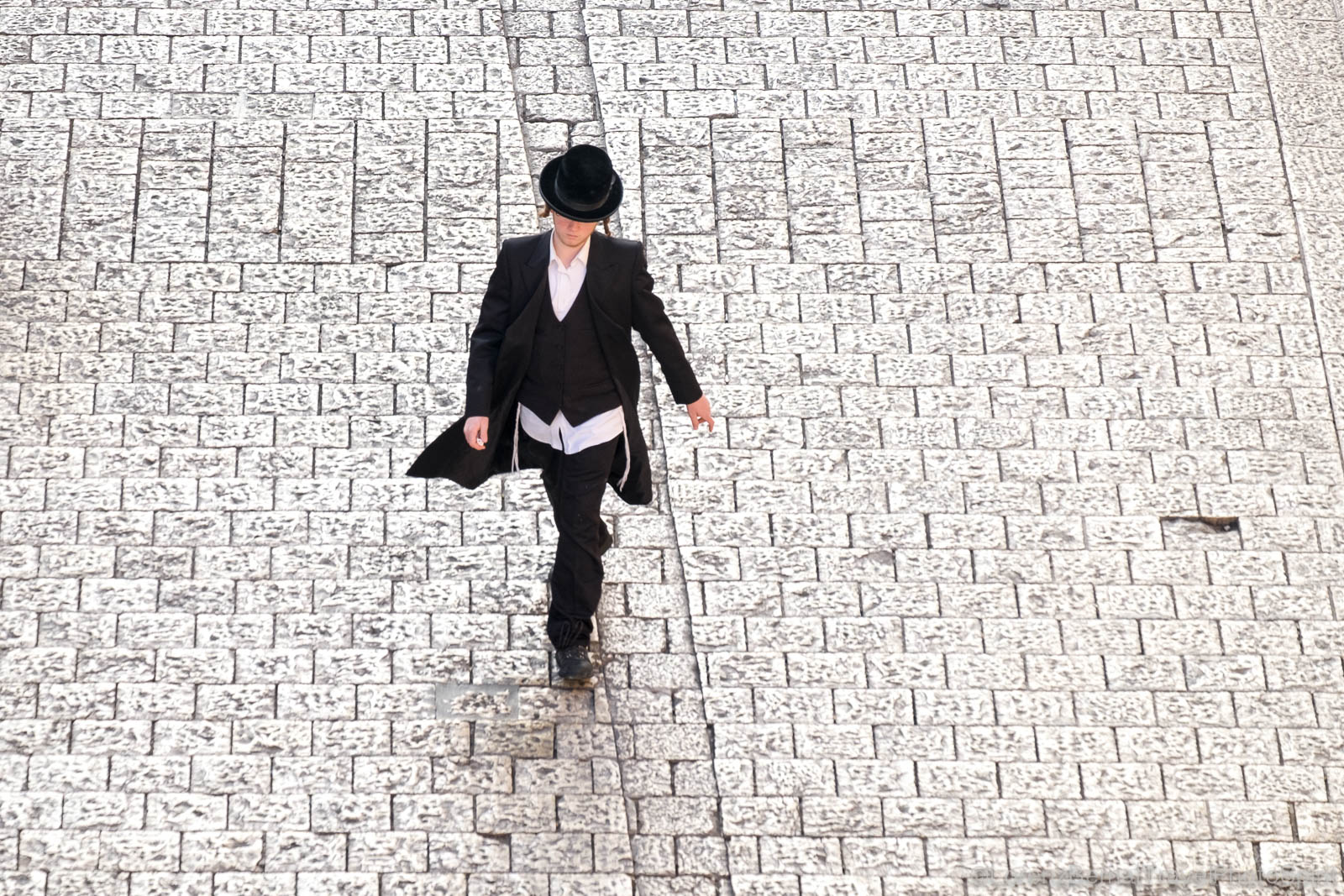 Jerusalem Street photography : photo from above of a young jewish man passing by in a paved street of the old city.