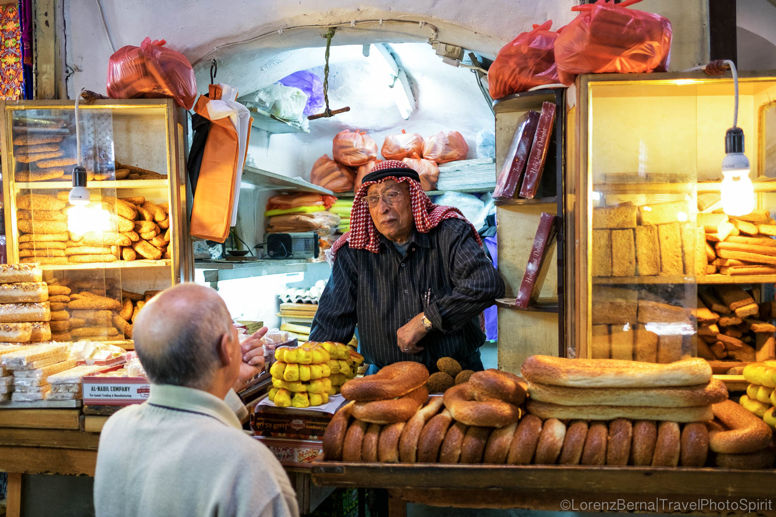 Two men talking at a local food stall in the Muslim Quarter, Jerusalem, Israel.