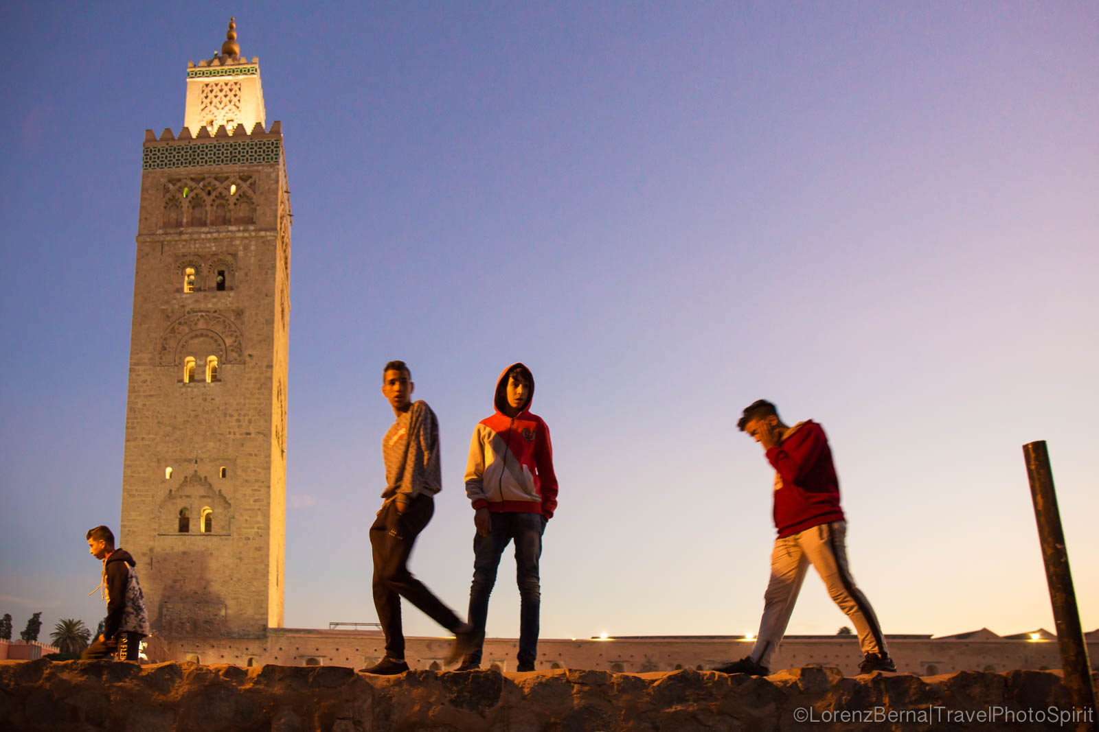 Young Moroccans walking over the ancient walls of the Koutoubia Mosque in Marrakech, after sunset. Best of Marrakech photo guide.
