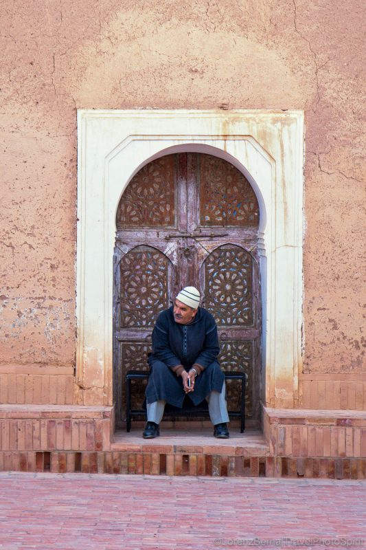 Man sitting at a traditional wooden carved door in Tinghir