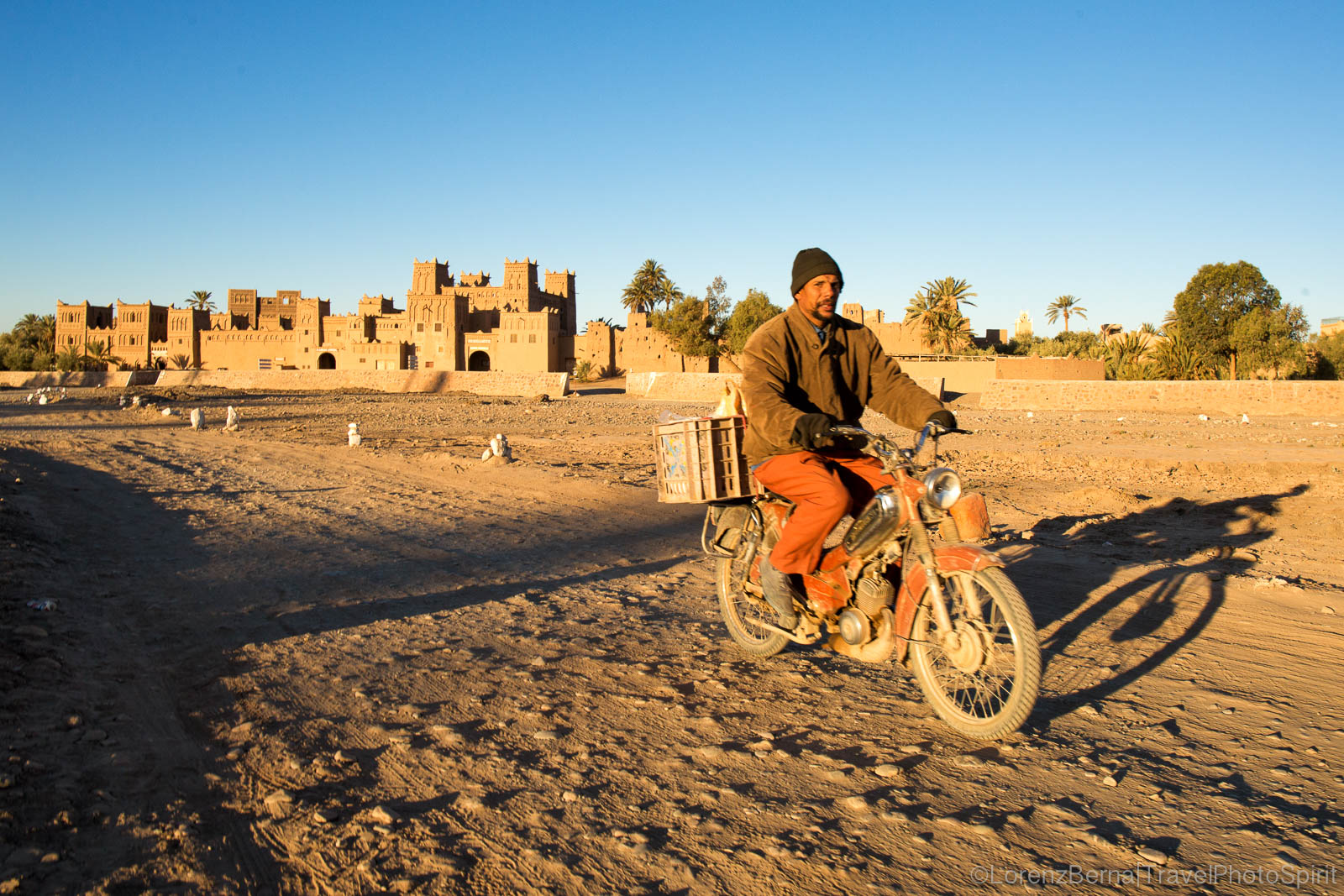 Local man on motorbike passing in front of the Amerhidl Kasbah in Skoura, Morocco