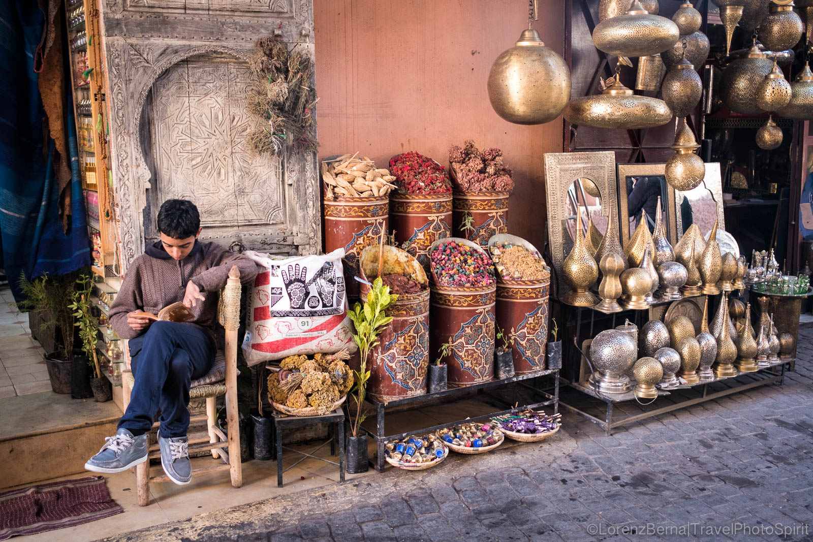 Afternoon in Marrakech Medina : boy at his stall playing on his phone while waiting for customers