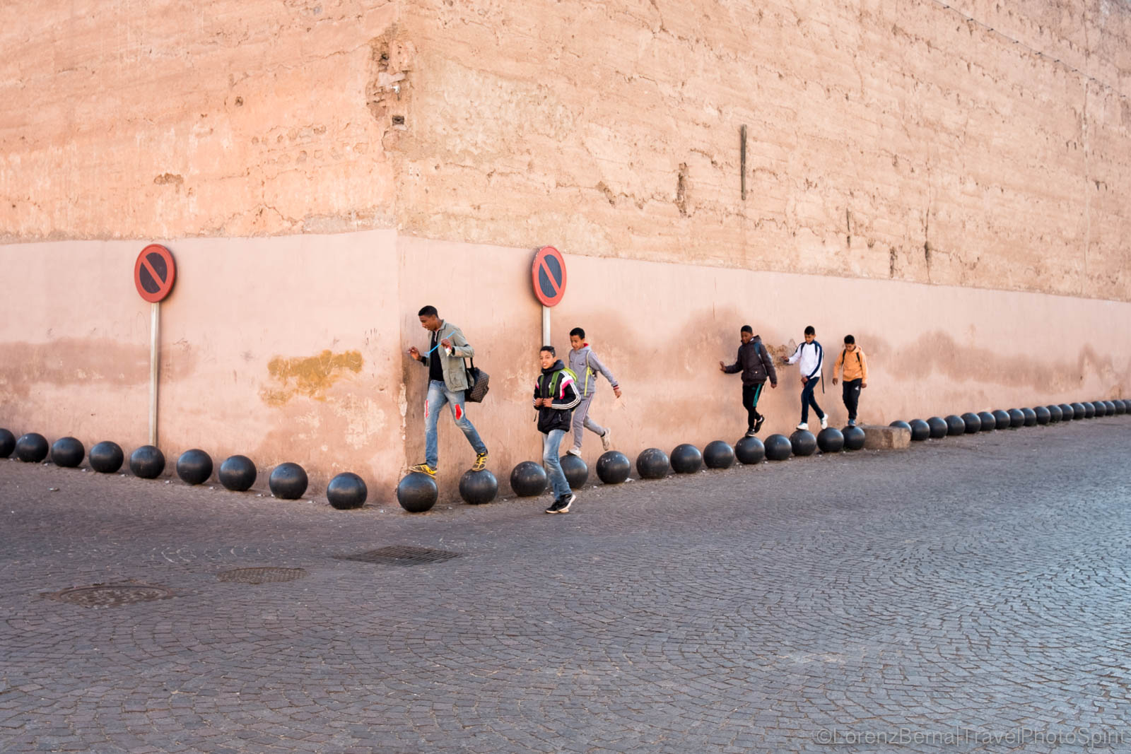 Group of boys walking over street bollards alongside a city rampart in Marrakech