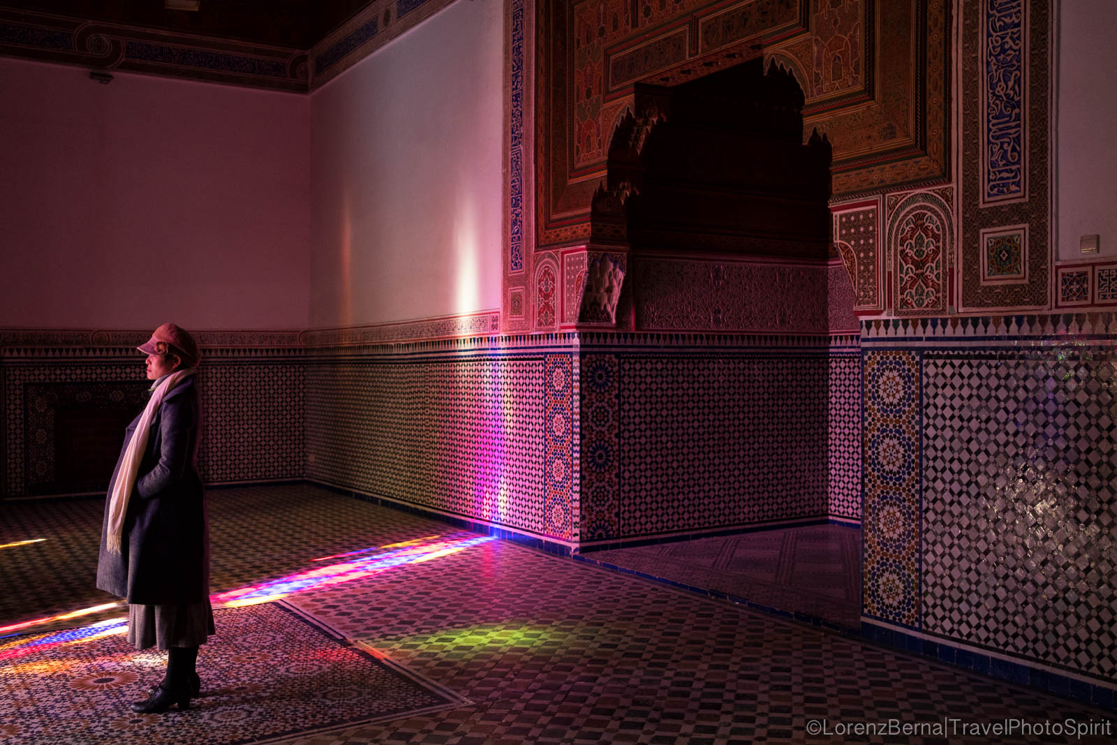 Woman framed within some colourful reflections inside of 'El Bahia' Palace of Marrakech.