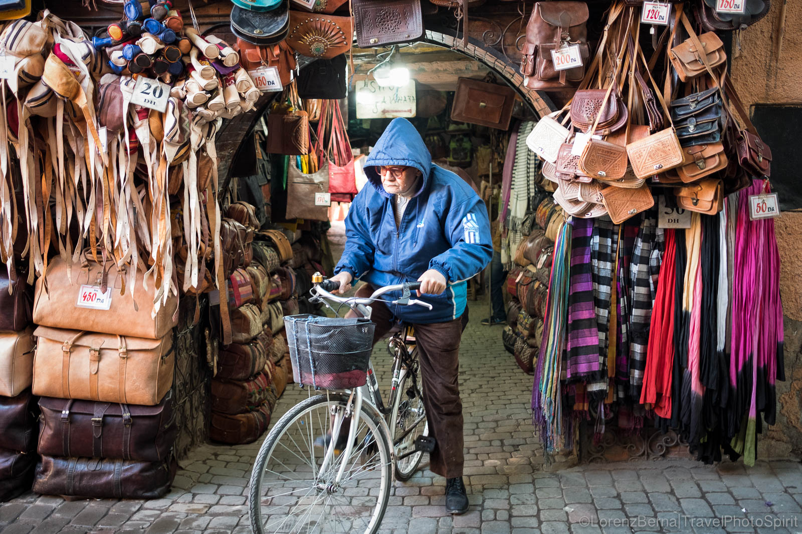 A man in front of a leather stall in a Marrakech souk