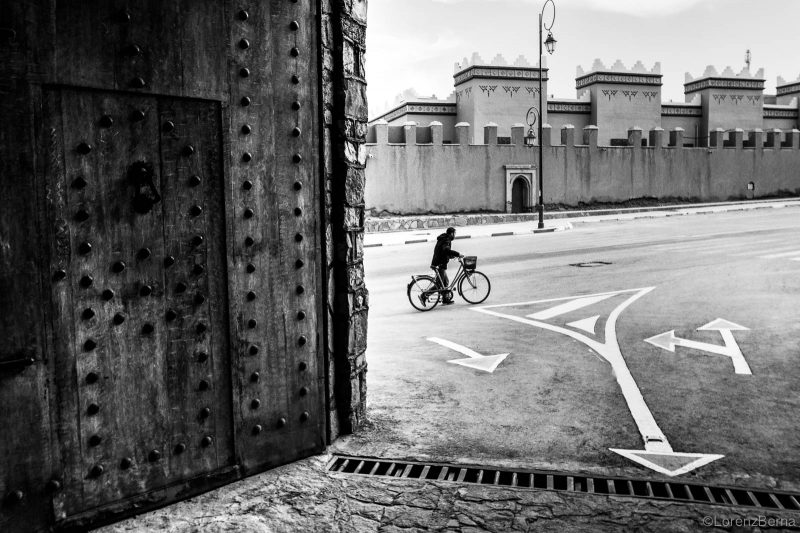 Morocco Street Photography by professional travel photographer Lorenz Berna : Local man cycling in front of a traditional Kasbah in Midelt, Atlas region of Morocco.