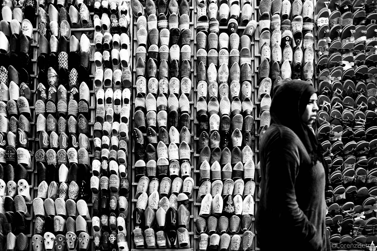 Woman in front of a street shoe stall in Fez, Morocco