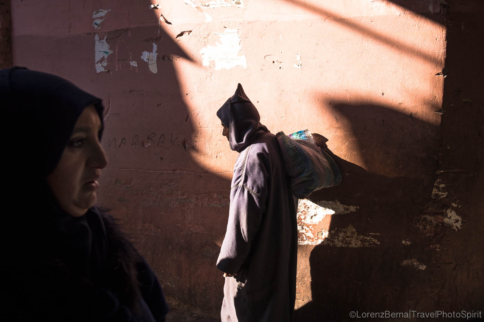 Street photography in Marrakech : a man with the traditional hooded Djellaba passing in front of a colourful wall.