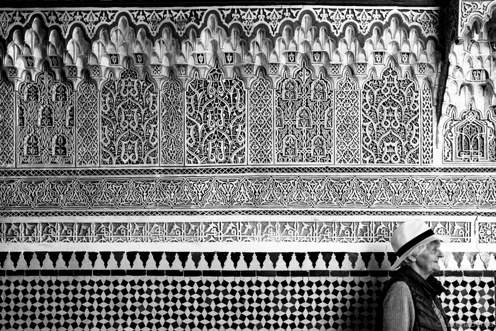Woman passing by a refined wall carved in marble and covered with mosaics.