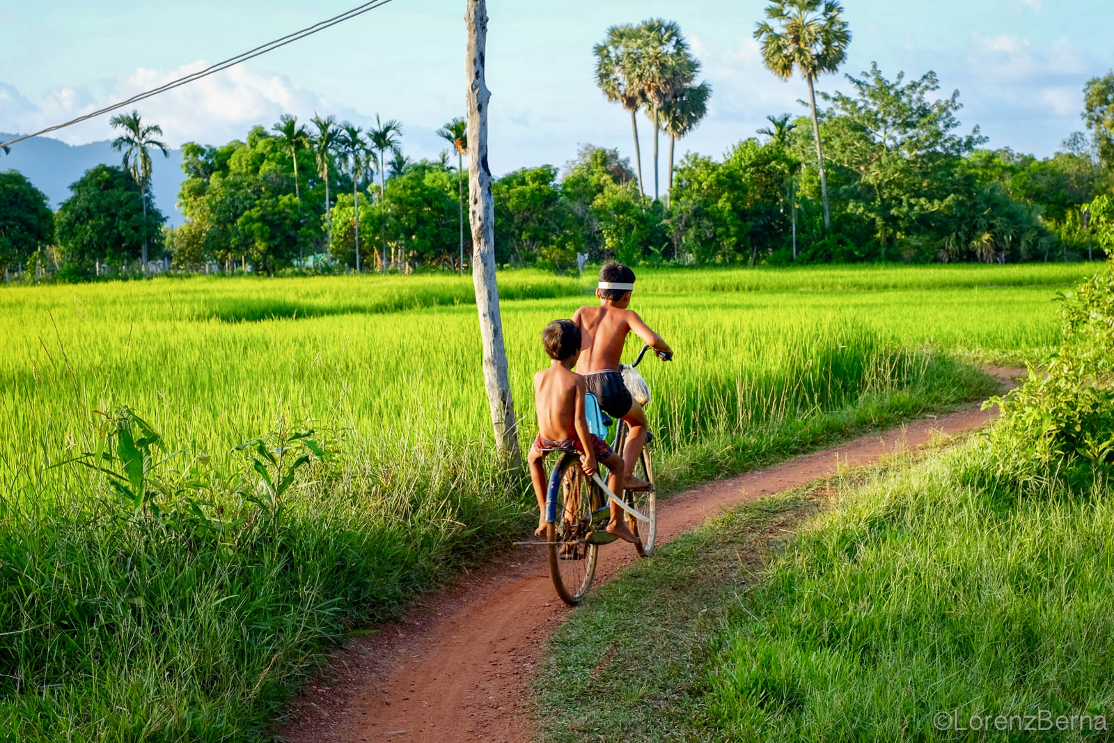 Cambodian kids cycling in Kampot countryside - Cambodia Travel Photography
